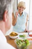 Mujer que habla con el marido como ella prepara la comida de A Imágenes de archivo libres de regalías