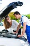 Mujer que habla con el mecánico de coche en el taller de reparaciones Foto de archivo libre de regalías