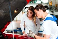 Mujer que habla con el mecánico de coche en el taller de reparaciones Imagen de archivo libre de regalías