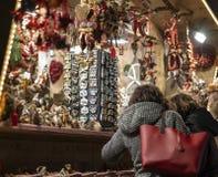 Mujer que habla con la situación del amigo delante de la cabina del mercado de la Navidad en el sur el Tyrol del merano imagen de archivo