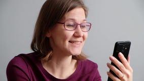Mujer que habla con su amigo vía Skype o la llamada video en smartphone almacen de metraje de vídeo