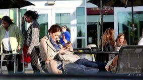 Mujer que habla con su amigo y café de consumición de Starbucks almacen de video