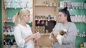 Mujer que habla con una dependienta en una tienda del veterinario para los animales domésticos, las píldoras de compra y la comid almacen de video
