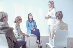 Mujer que habla de problemas a la gente joven durante terapia con el psicoterapeuta imagenes de archivo