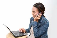 Mujer que habla el teléfono móvil y que usa el ordenador Imágenes de archivo libres de regalías