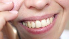 mujer que habla en el smartphone y el primer sonriente Muchacha que habla en risas de un teléfono celular, primer de los dientes foto de archivo