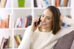 Mujer que habla en el teléfono en casa en invierno Foto de archivo libre de regalías