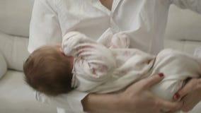 Mujer que habla en el teléfono con el bebé en sus brazos almacen de metraje de vídeo