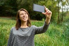 Mujer que habla en el teléfono en el parque imagenes de archivo