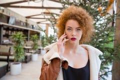 Mujer que habla en el teléfono en restaurante Fotos de archivo
