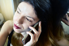 Mujer que habla en el teléfono móvil en casa Imágenes de archivo libres de regalías