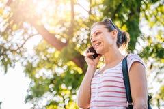 Mujer que habla en el teléfono móvil en el parque Fotografía de archivo libre de regalías