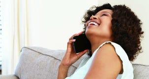 Mujer que habla en el teléfono móvil en la sala de estar 4k metrajes