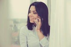 Mujer que habla en el teléfono móvil mientras que hace una pausa la ventana en el apartamento Imágenes de archivo libres de regalías