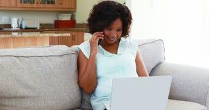 Mujer que habla en el teléfono móvil mientras que usa el ordenador portátil en la sala de estar 4k metrajes