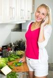 Mujer que habla en el teléfono móvil y que prepara la ensalada Imágenes de archivo libres de regalías