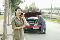 Mujer que habla en el teléfono mientras que mecánico Fixes Her Car Imágenes de archivo libres de regalías