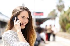 Mujer que habla en el teléfono que espera en una estación de tren Imágenes de archivo libres de regalías