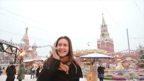 Mujer que habla en el teléfono que se coloca en el invierno en la Plaza Roja en Moscú, delante del Kremlin y de la catedral de la almacen de metraje de vídeo