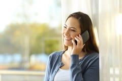Mujer que habla en el teléfono que se coloca en casa Imagen de archivo