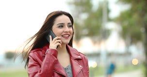 Mujer que habla en el teléfono en un parque metrajes