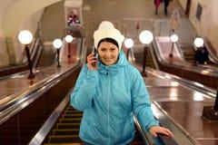 mujer que habla en el teléfono en una escalera móvil en subterráneo Fotografía de archivo