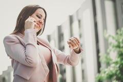Mujer que habla en el teléfono y que comprueba el tiempo en el reloj foto de archivo