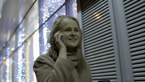 Mujer que habla en el teléfono y el café de consumición mientras que metrajes