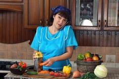 Mujer que habla en el teléfono y las zanahorias de las frotaciones en un rallador Fotografía de archivo