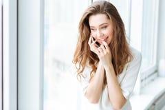 Mujer que habla en el teléfono y que mira en ventana Fotografía de archivo libre de regalías