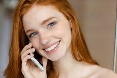 Mujer que habla en el teléfono y que mira la cámara Imagenes de archivo