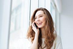 Mujer que habla en el teléfono y que mira la ventana Imagen de archivo
