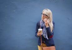 Mujer que habla en el teléfono y que sostiene la taza de café mientras que se coloca en la pared fotos de archivo libres de regalías