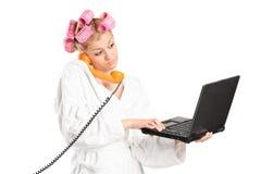 Mujer que habla en el teléfono y que trabaja en el ordenador portátil Fotografía de archivo