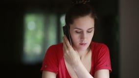 Mujer que habla en el teléfono en casa almacen de metraje de vídeo