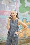 Mujer que habla en fondo de la pared de la pintada del smartphone Foto de archivo libre de regalías