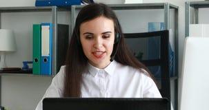 Mujer que habla en las auriculares en oficina moderna almacen de video