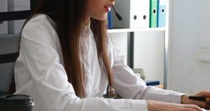 Mujer que habla en las auriculares y que usa el ordenador portátil en oficina moderna almacen de metraje de vídeo