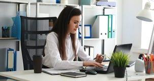 Mujer que habla en las auriculares y que usa el ordenador portátil en oficina moderna almacen de video