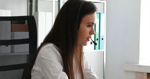 Mujer que habla en las auriculares y que usa el ordenador portátil en oficina moderna metrajes