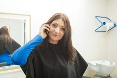 Mujer que habla en salón del peluquero de AR del teléfono Imagen de archivo