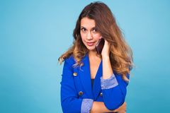 Mujer que habla en su teléfono celular sobre un fondo azul Imagen de archivo