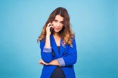 Mujer que habla en su teléfono celular sobre un fondo azul Imagen de archivo libre de regalías