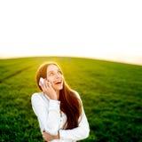 Mujer que habla en teléfono en el campo verde Imagen de archivo
