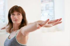 Mujer que hace actitud de la yoga de Virabhadrasana en gimnasio Imagen de archivo libre de regalías