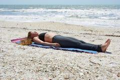 Mujer que hace actitud del cadáver de la yoga en la playa Fotografía de archivo
