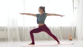 Mujer que hace actitud del guerrero de la yoga en el estudio almacen de metraje de vídeo