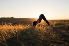 Mujer que hace actitud hacia abajo del perro de la yoga durante puesta del sol Imagen de archivo