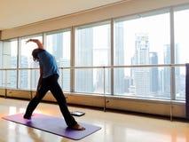 Mujer que hace actitud lateral del triángulo en estudio de la yoga Foto de archivo libre de regalías