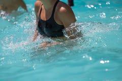 Mujer que hace aeróbicos de agua en una piscina al aire libre Imagen de archivo